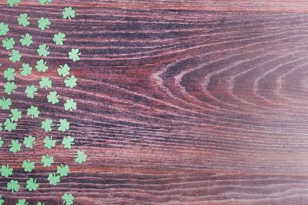Green clover leaves on a wooden background. Background for St. Patricks Day. Space for text. Paper decorations