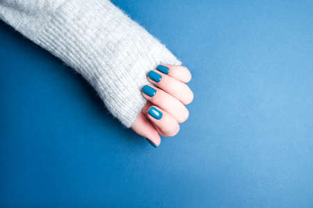Beautiful female manicure on a blue background. Blue manicure on well-groomed hands.
