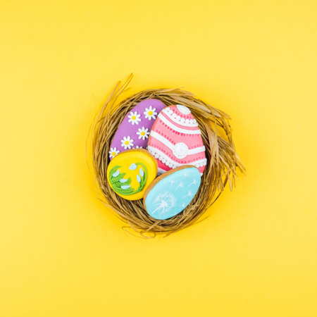 Nest with Easter eggs on a yellow background. Cookies decorated with Easter eggs. Stylish background for Easter. Zdjęcie Seryjne