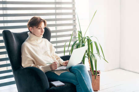 Young girl works or studies with laptop in headphones while sitting in armchair in pleasant atmosphere at home. She has pen in hands, and notebook lies nearby. The background is bright, almost white. 版權商用圖片
