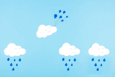 White cut-out clouds on a blue background. To be not like others, positive thinking, to see only the good. The concept of getting out of your comfort zone and turning the situation around