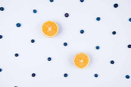 Blueberries on a white background and orange slices. Pattern with berries and fruit