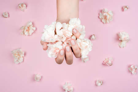 Well-groomed female hand with a neat manicure. Flowers are taken in a handful. Pink background with a scattering of flowers. The concept of self-care