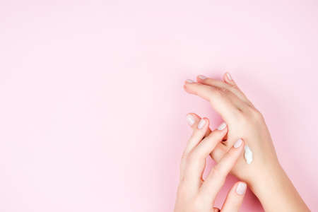 Gentle well-groomed female hands with Nude manicure. The girl smears her hands with cream. The concept of skin care. Copyspace for text