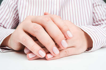 Delicate well-groomed female hands with Nude manicure close-up Banque d'images