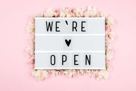 Were open lettering on a lightbox on a pink background surrounded by flowers. A message from the owner of a business, cafe, or beauty salon.