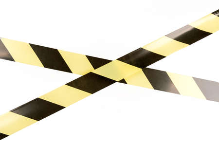 Black and yellow restrictive tape on a white background. The tape is crossed, restriction.