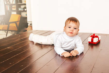 A little girl is crawling on the floor of the house. The baby runs away from her mother. Gift box next to the child. Cozy house with wooden floors