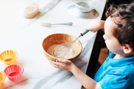 A little boy prepares chocolate muffin dough. The kid licks the chocolate off the spoon. Leisure with children at home. Little boy preparing muffin dough stirring mixture with whisk