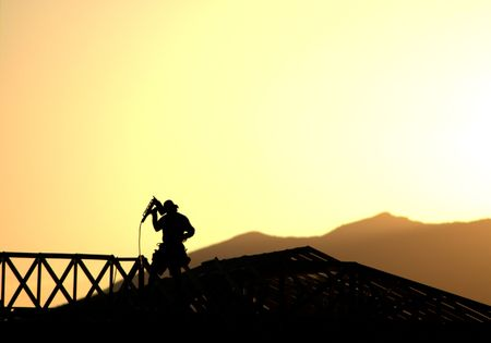 joists: Silhouette of construction worker framing a new home at sunset against a mountain backdrop. Stock Photo