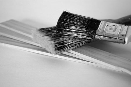 Black and white image of two grubby, well-used paint brushes with three wooden paint stirrers.  Home improvement theme.