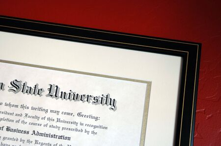 University degree framed and hanging on textured red wall. Banco de Imagens