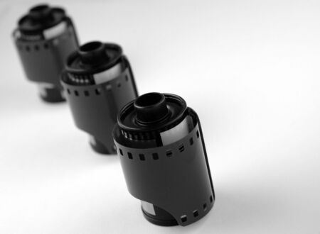 lack & White Image of unexposed 35mm film rolls. Three in a line, shallow depth of field with focus on first roll. Banco de Imagens
