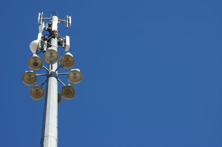 Image of tall communication tower and light pole against deep blue sky.