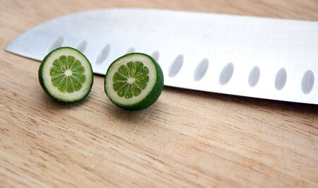 Tiny baby lime on cutting board with chefs knife.  Strange perspective with tiny lime and large knife.