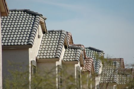 Acacia trees frame track houses lined up in a desert Southwest neighborhood. Banco de Imagens