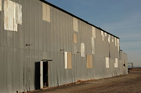 Abandoned agricultural warehouse with open side door. Past repair work can be clearly seen. Banco de Imagens
