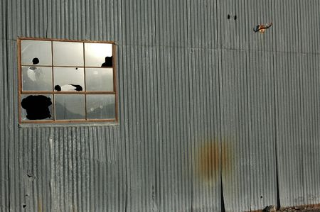 Broken Window on abandoned warehouse.  Suggests outdated or abandoned industry.  Image framed with room for possible copy.