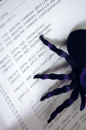 Image of spider on hardcopy of computer code. Indicates bugs or errors or problems with computer programs or software. Shadows from