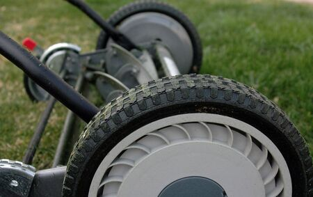 Old style push reel mower.  Mower photographed dirty to show extended use.  Perspective shot of wheels and blades with shallow depth of field set against green grass background.
