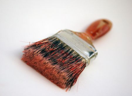 Grungy well-used paintbrush on white background.  Brush bristles show several colors of paint that the brush was used with.  Limited depth of field, focus on brush bristles.