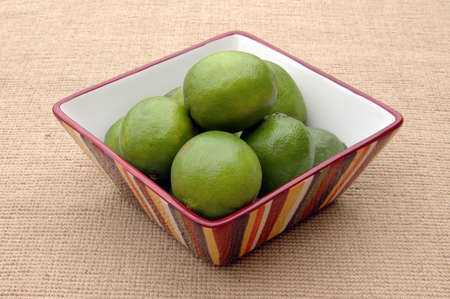 Ripe limes in a colorful striped bowl on burlap cloth