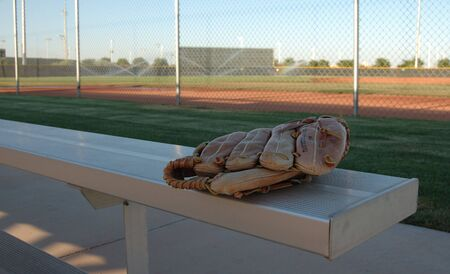 dugout: Image of a baseball glove on a fan bleacher.  The ball field is seen being watered in the background . Stock Photo