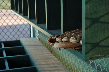 baseball dugout: Image of a baseball glove on a shelf in an empty dugout. Stock Photo