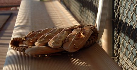 The soft glow of sunset falls on a baseball glove left on the bench after the game.