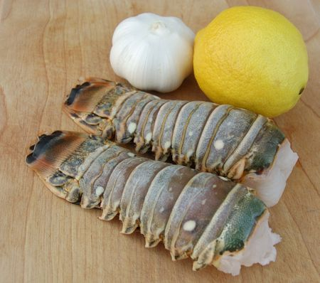 Delicious lobster tails with ripe lemon and sweet garlic on a wooden cutting board.  Perfect for summer grilling! Stock Photo - 439944