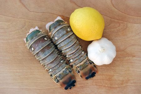 Delicious lobster tails with ripe lemon and sweet garlic on a wooden cutting board.  Perfect for summer grilling!