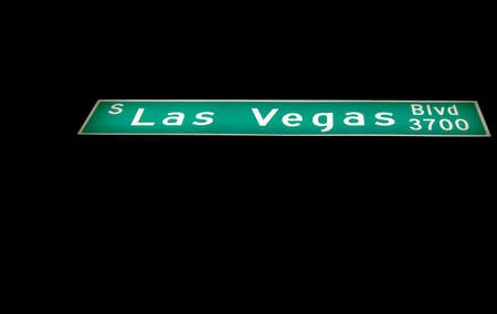 Perspective image of illuminated Las Vegas Boulevard street sign against black night background.