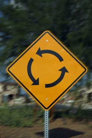 futile: Image of a traffic circle sign with motion blur added for effect.  Represents circular logic, confusion or futile effort. Stock Photo