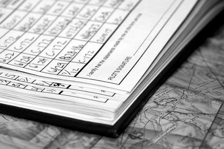 entries: Private Airplane Pilot logbook with full page of entries showing date, airplane and airports on navigational chart. Shallow depth of field in black & white.