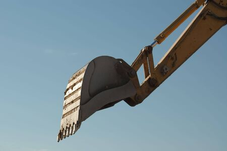 Close-up shot of trackhoe bucket at work against the blue sky morning. Stok Fotoğraf