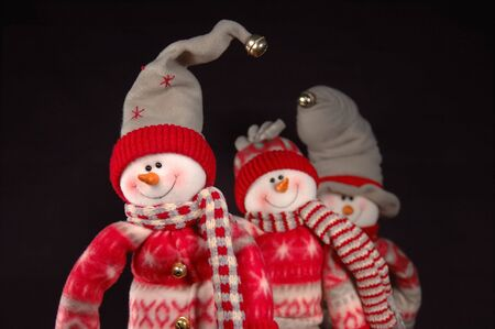 Three happy snowpeople lined up.  Shallow depth of field with focus on front snowperson
