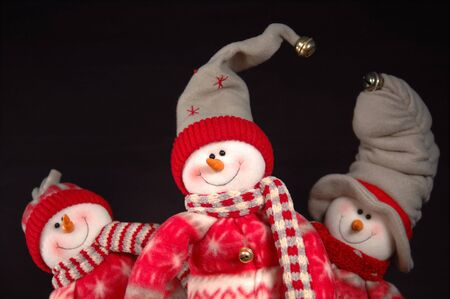 Three snowpeople posing whimsically for the camera.