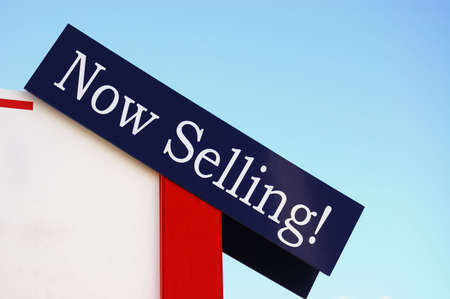 Image of colorful Now Selling! Sign against blue sky background. Stok Fotoğraf
