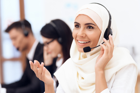 An Arab woman works in a call center. Arabian works at office as operator. Her colleagues work nearby.