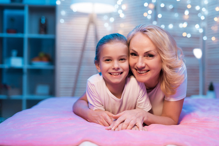 Grandmother and granddaughter are hugging on bed at night at home. Grandma and child on bad.