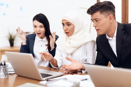 The Arab woman in hijab works in the office together with her colleagues. They are engaged in business. On the desk is a laptop.