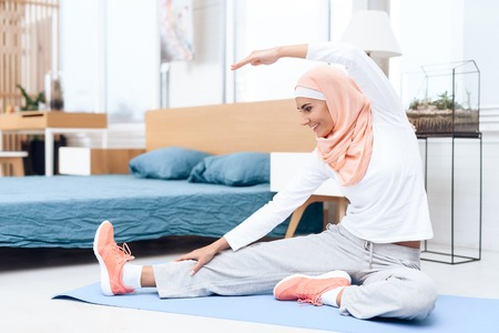 Arab woman doing gymnastics in the bedroom. She's at home. She has a headscarf on her head.