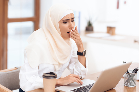 Arab woman wearing a headscarf sitting tired at work. She yawns. She is sitting at the desk in the office.
