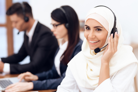 An Arab woman works in a call center. She's an operator. Her colleagues work nearby.