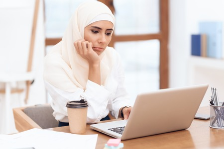 Arab woman wearing a headscarf sitting tired at work. She is sitting at the desk in the office. Stock Photo