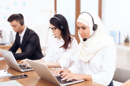 An Arab woman works in a call center. Shes an operator. Her colleagues work nearby. Stock Photo