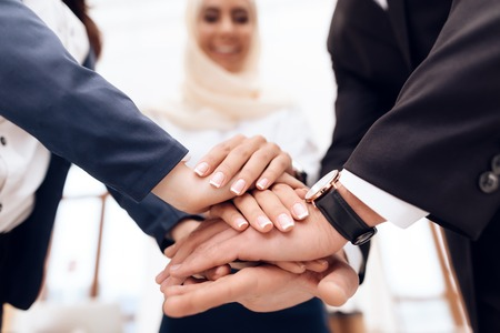 Two women and a man are holding each others hands. One woman is arab. They demonstrate teamwork. Stock Photo