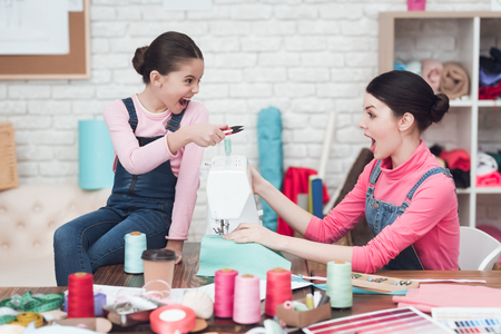 Little girl gives a woman scissors. They are with mom in the sewing workshop. Mom sews on the sewing machine. 写真素材