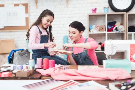 ママと娘はジュエリーを選ぶ。彼らは縫製のワークショップで一緒に働きます。彼らは機嫌がいい。