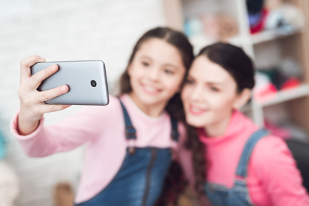 Mom with a little girl do selfie on a smartphone. They are together in a sewing workshop. They are in a good mood.